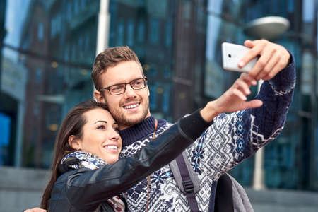 Happy love couple of tourists taking selfie in urban city Foto de archivo