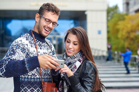 Happy couple with smart phone. Happy young loving couple standing outdoors together and looking at the mobile phone together Foto de archivo