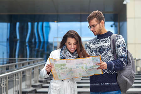Couple of young tourists reading a map and searching location in the city