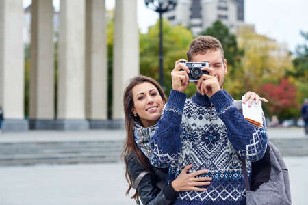 Happy love couple of tourists taking photo on excursion or city tour. Travel together with a map and retro camera