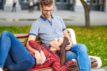 Lovely portrait of a young couple. They are sitting on the bench, embracing and kissing. Foto de archivo