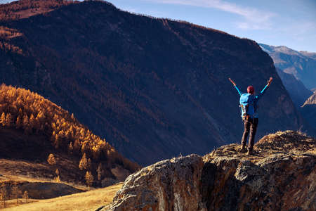 Hiker woman with backpack on rock of a mountain and enjoying sunrise. Travel Lifestyle success concept adventure active vacations outdoor mountaineering sport