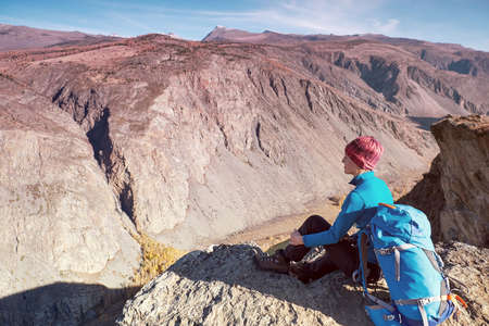 Hiker woman with backpack sitting on rock of a mountain