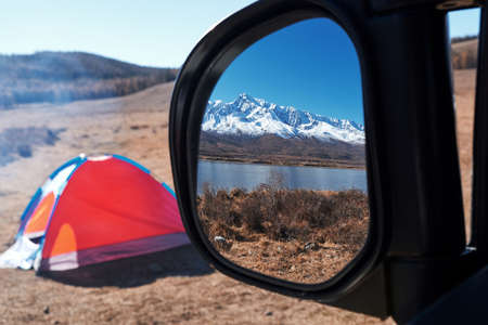 Landscape reflected in the rearview mirror of a car in Altai. Camp with tents, travelers going on the road