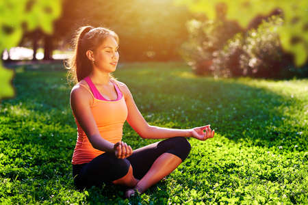 Yoga. mixed race woman practicing yoga or dancing or stretching in nature at park. Health lifestyle concept