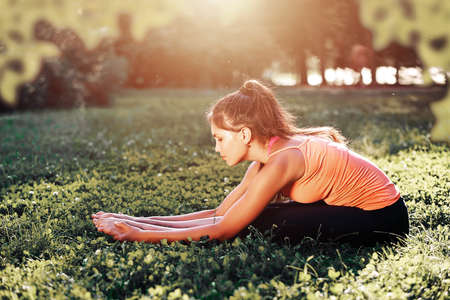 Yoga. Young woman practicing yoga or dancing or stretching in nature at park. Health lifestyle concept Foto de archivo