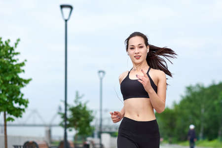 Running asian athlete woman. Morning jogging.