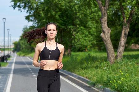 Running asian woman on running track. Morning jogging. The athlete training Foto de archivo