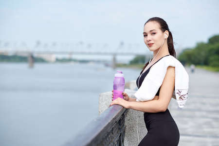Fitness healthy asian woman runner relaxing after running outdoors enjoying view on waterfront Foto de archivo