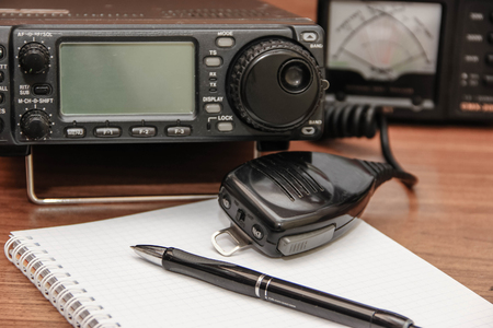 transceiver: Radio transceiver, microphone and a notebook. Stock Photo