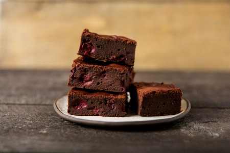Brownie dessert slices with cherry on a plate, wooden background, close-up Фото со стока