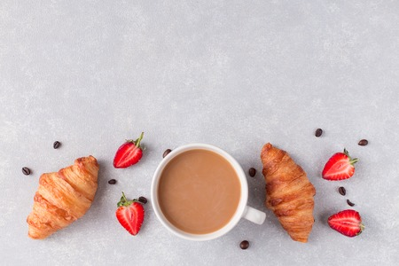 Coffee Cup Strawberry two croissants on a grey background, free space