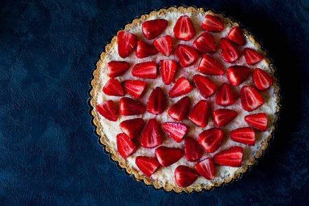Fresh strawberry pie on dark blue background, top view, free space