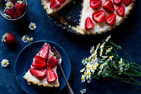 Fresh strawberry pie on dark blue background, top view, decor, chamomile, one piece on the plate Standard-Bild