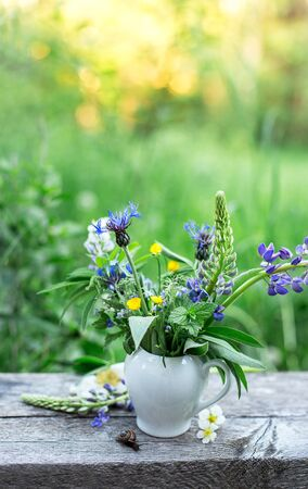 Stilllife with vase with wild flowers and snail on the old wooden table on the nature, sunset, blur Reklamní fotografie