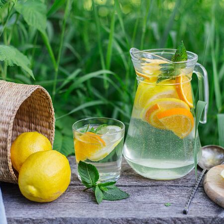 fresh lemonade and a glass on wooden old table against a backdrop of green grass, day