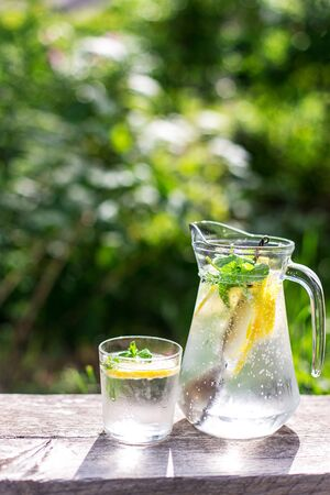 fresh lemonade and a glass on wooden old table against a backdrop of green grass, day Imagens - 126059507