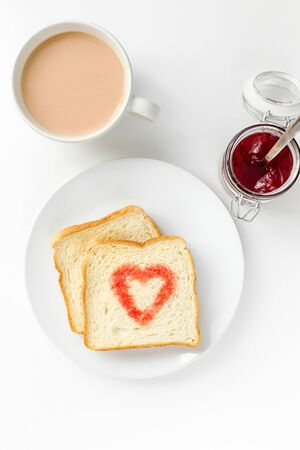 Breakfast with cup of tea, toast heart of berry jam top view