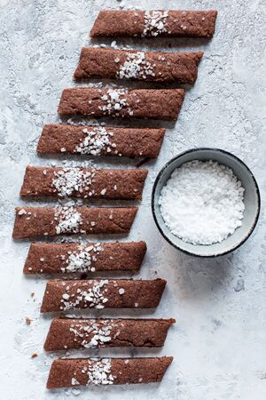 chocolate biscuit strips with sugar on a grey background, top view