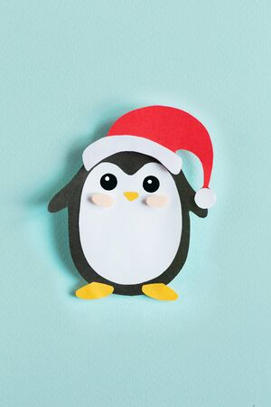Christmas penguin from paper on a blue background, top view