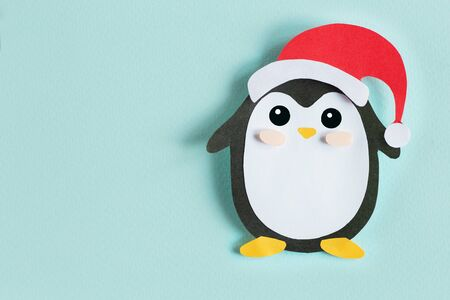 Christmas penguin from paper on a blue background, top view, horizontal Stock Photo