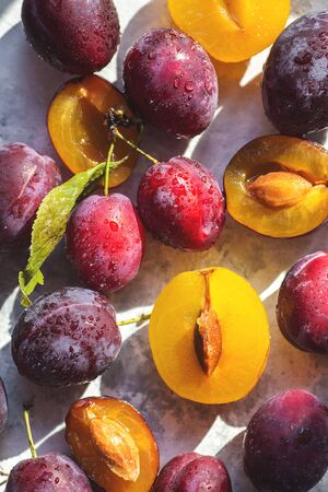Many fresh plums on sunny light grey background isolated, top view