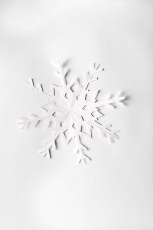white background with one big paper snowflakes, top view