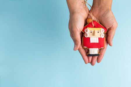toy nutcracker in hand on a blue background, free space for your text