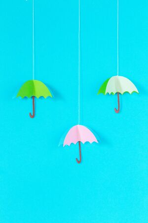 blue background with an umbrella on a rope of paper, handmade