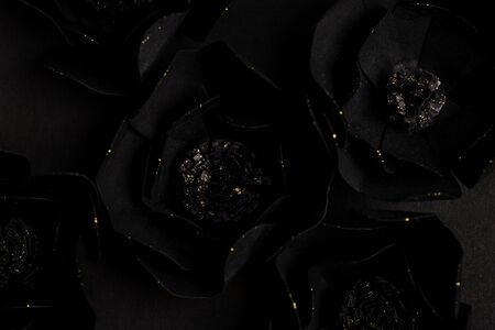 black background with a beautiful gold glittering flowers made of paper, top view, macro