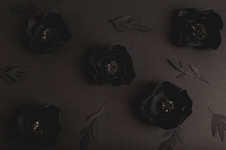 black background with a beautiful gold glittering flowers made of paper, top view