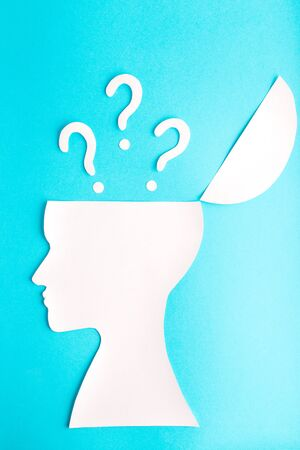 Blue background with white many question from head, paper, woman face, profile, psychology