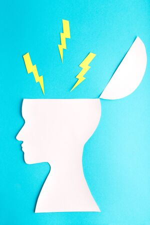 Blue background with yellow lightning from head, paper, woman face, profile, psychology, angry