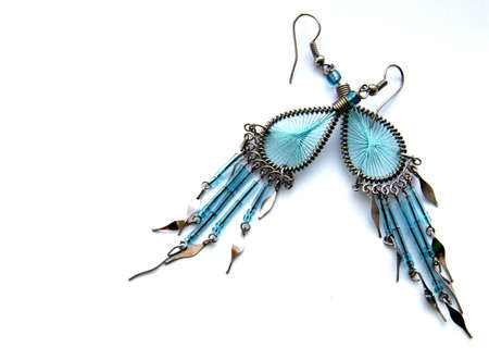 Original earrings from metal and blue glass on a white background
