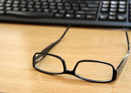Glasses in a black frame on a table against the keyboard