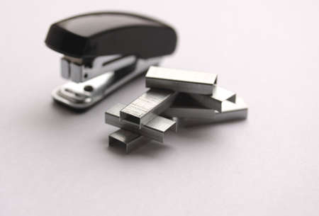 Clips and stapler on light grey background (small depth of sharpness)