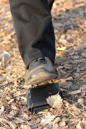 Autumn financial crisis (Male foot attacks a wallet against the autumn fallen down leaves)