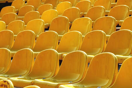 Empty rows of yellow plastic chairs