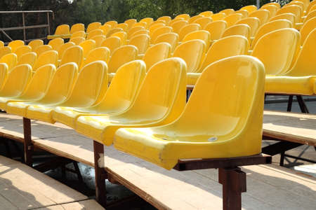 Empty rows of yellow plastic chairs on wooden scaffold Stock Photo