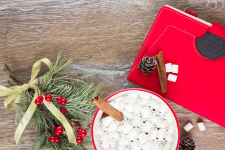 Cup of hot cocoa or chocolate with marshmallows, holiday decorations and laptop with to do list on turquoise vintage table from above, Christmas planning concept. Flat style. Imagens