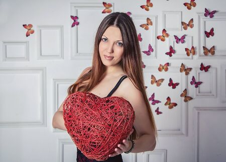 osier: Smiling beautiful woman holding osier heart in front of the wall decorated by frames and buterflies