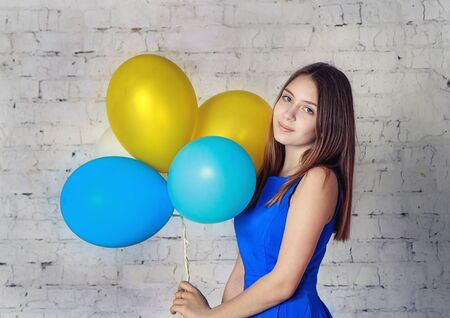 baloons: Beautiful teenager girl in blue dress with long hair holding colorful baloons
