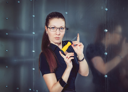 clincher: Serious attractive businesswoman wearing glasses holding screwdriver