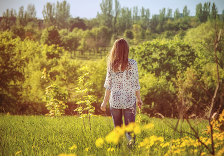 girl holding flower: Young woman walking away through the meadow holding yellow flowers