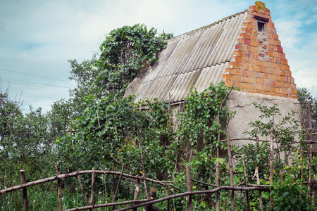 selfmade: Abandoned farm house in neglected garden with wooden selfmade hedge