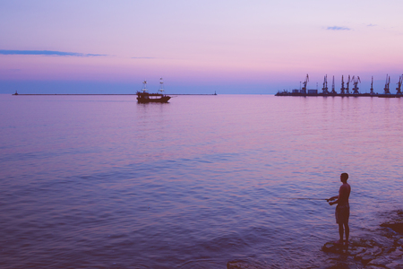 pleasure craft: Silhouettes of fisher on the seashore, dock cranes in the distance and sailing pleasure craft at sunset