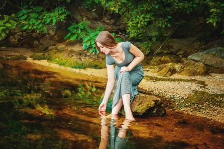 Aantrekkelijke jonge vrouw, gekleed in lange jurk zitten op de rots met de voeten in een weedy vijverwater Stockfoto