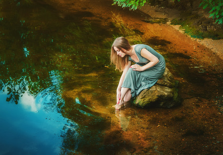long feet: Attractive young woman wearing long dress sitting on the rock touching her feet in a weedy pond water