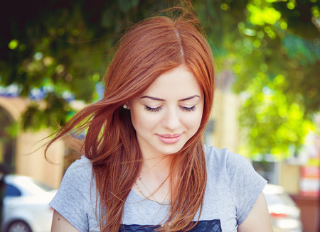 breeze: Pretty girl looking down with timid smile and her red hair waving in the breeze outdoors