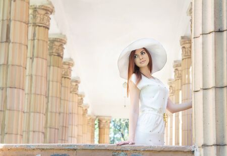 coolie hat: Beautiful young woman in white dress and  hat standing between old columns